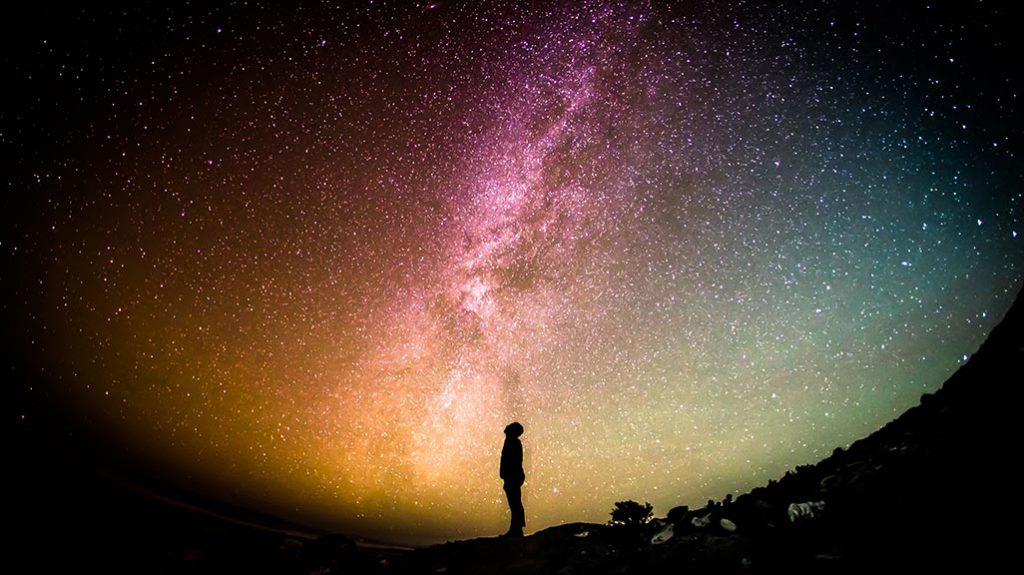 Homem a olhar para o céu estrelado