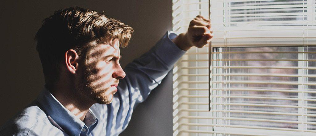 Homem a reflectir à janela