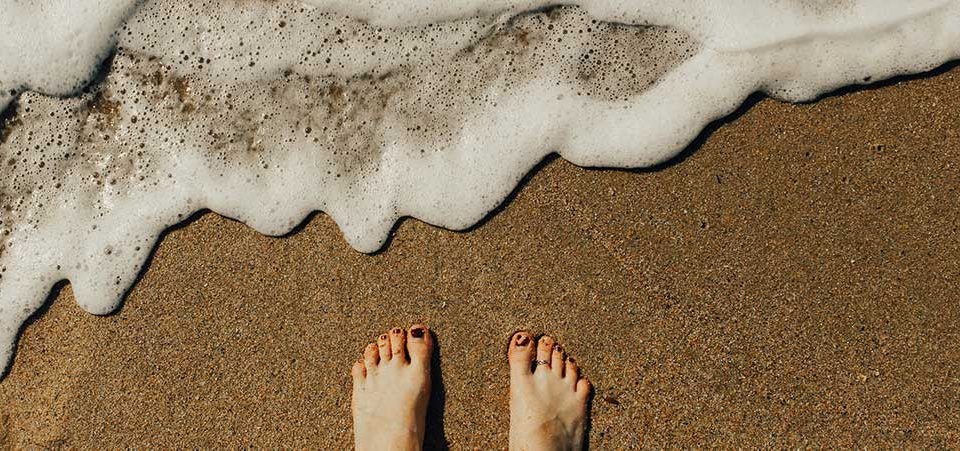 Pés à beira mar