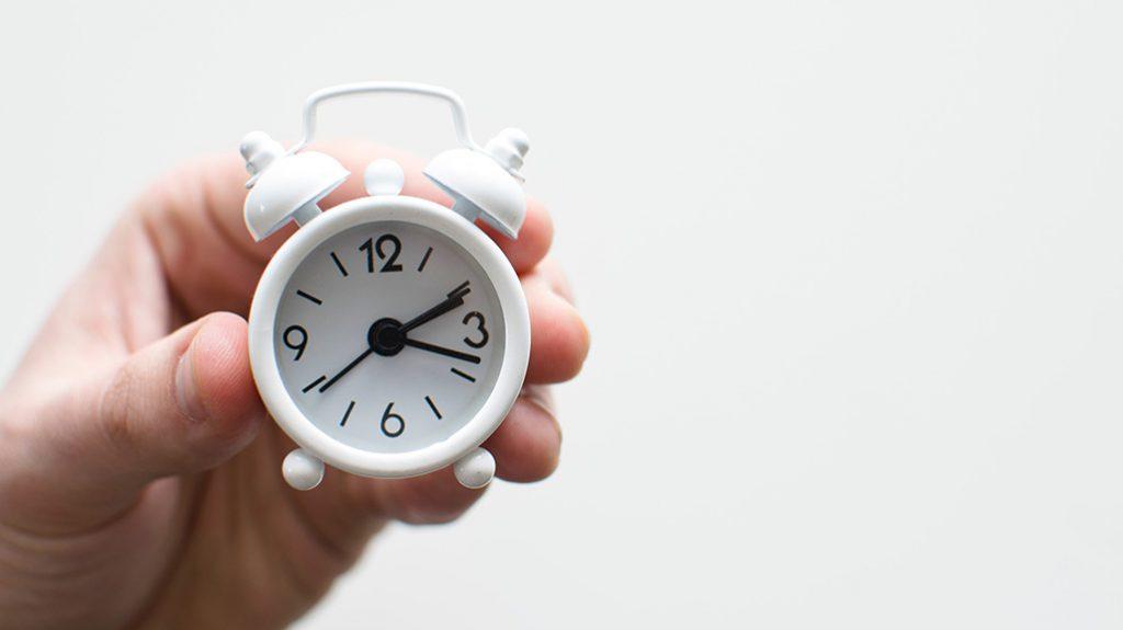 Mão a segurar relógio pequeno