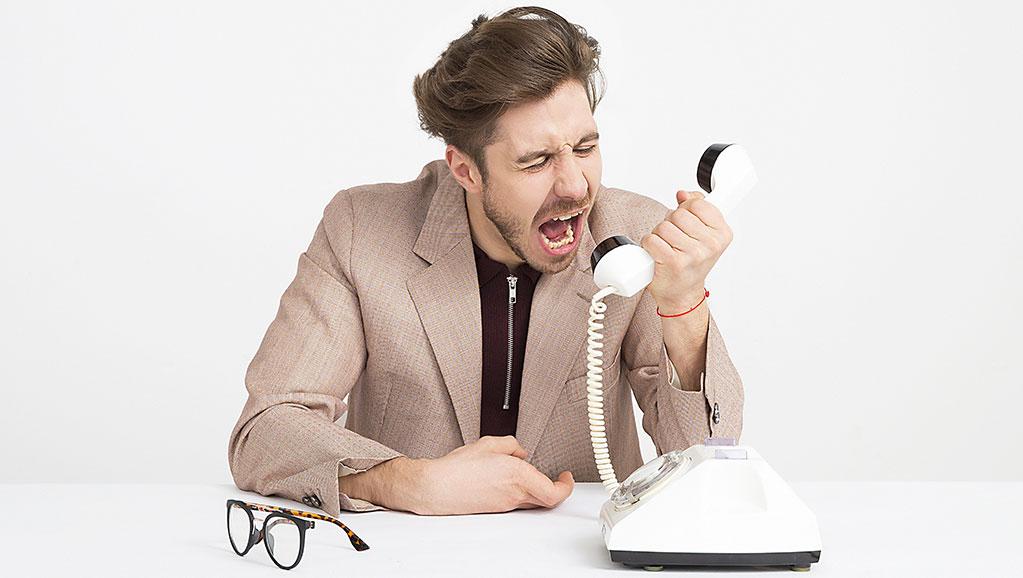Homem a gritar para um telefone