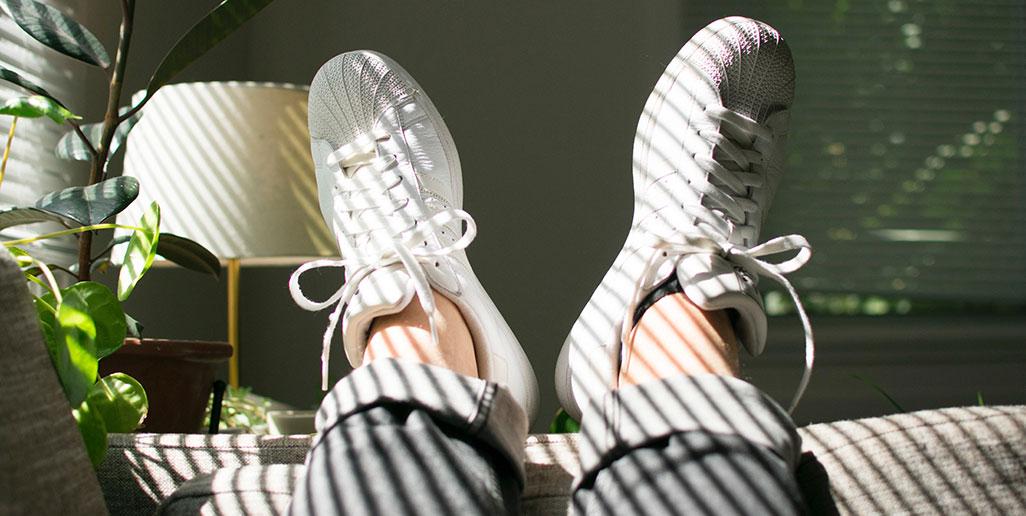 Pés calçados a relaxar no sofá