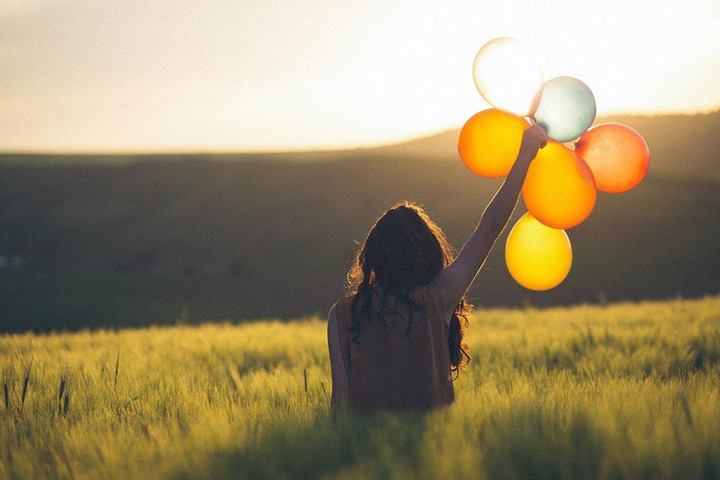 Mulher a segurar balões coloridos