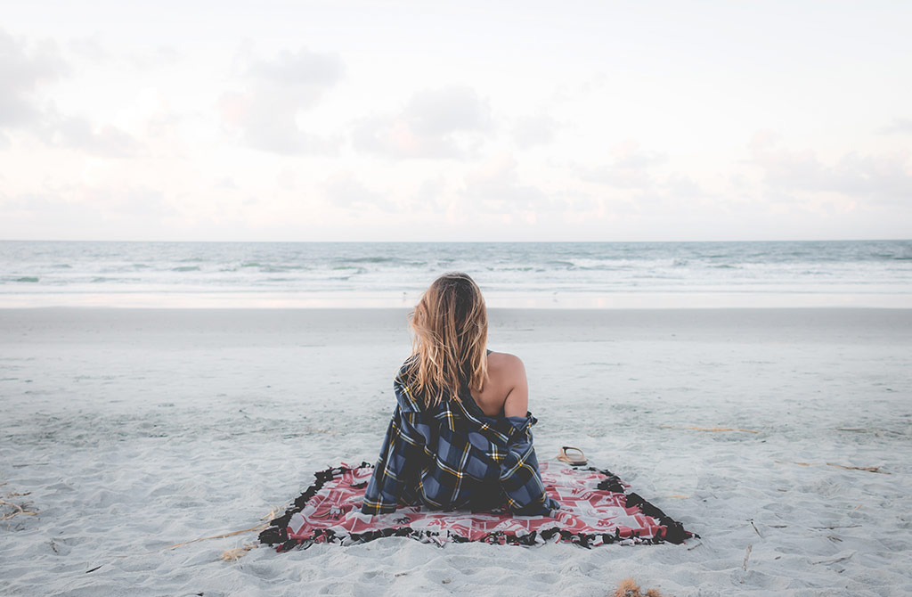 Mulher na praia a reflectir