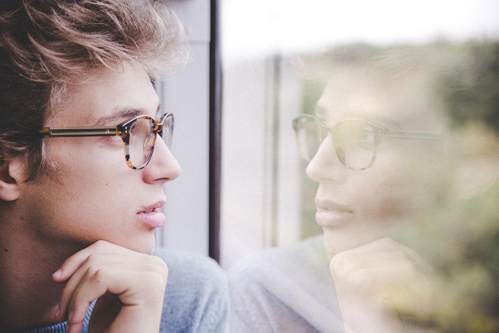 Rapaz pensativo à janela