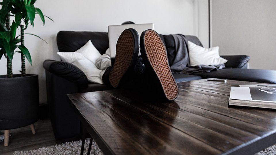 Homem a trabalhar no sofá em casa