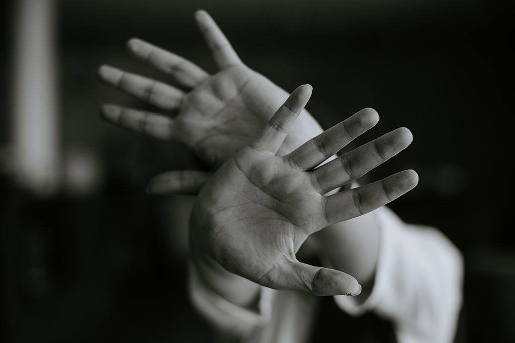 Mãos a proteger o corpo
