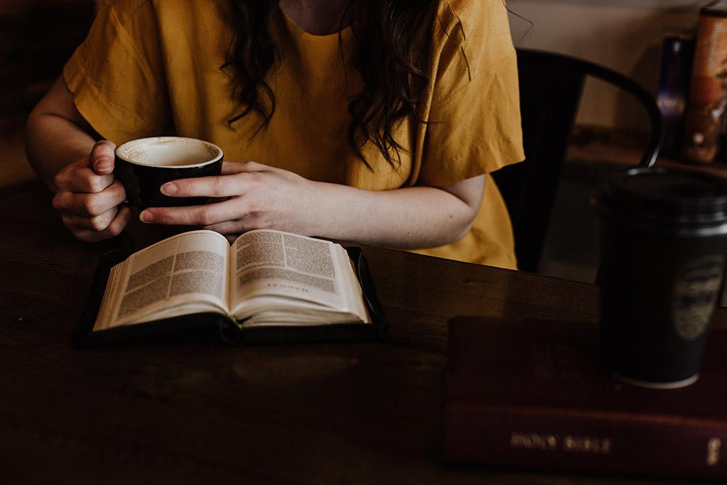 Rapariga a ler um livro e beber chá